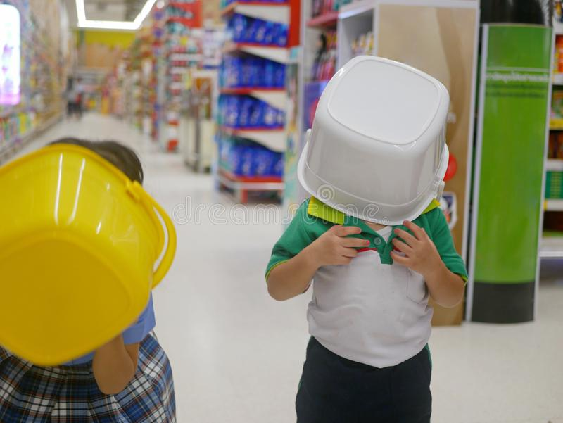 Little Asian baby girl right covering her head with a white plastic bucket, playing with her sister, at supermarket stock photo