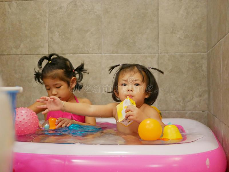 Little Asian baby girl right enjoys drinking milk and playing water, with her older sister, in a small pool in a bathroom royalty free stock photo
