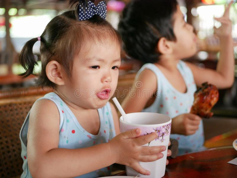 Little Asian baby girl`s hands lifting up a cup filled with water learning to drink water from a cup with straw by herself royalty free stock photography