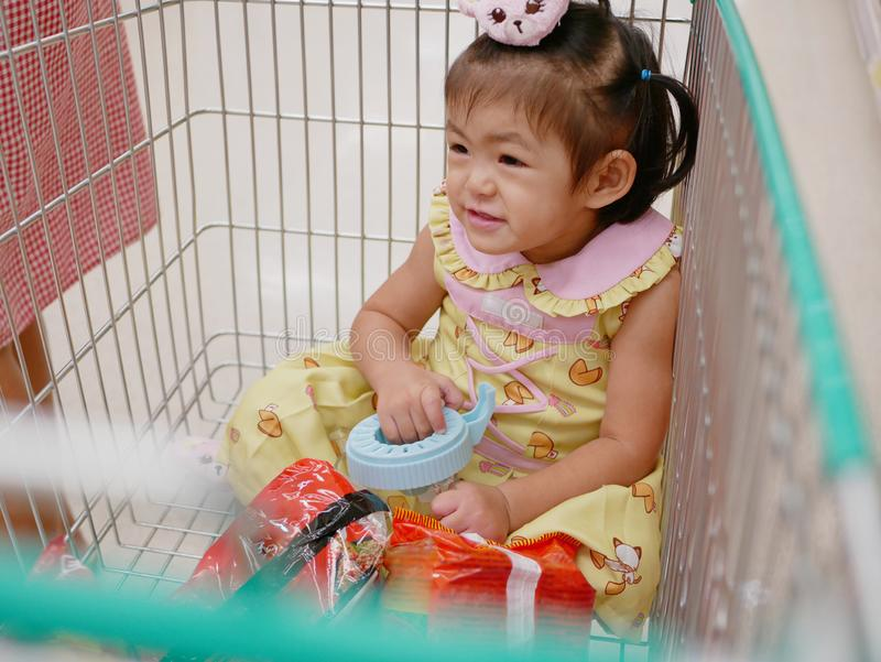 Little Asian baby girl sits in a shopping cart, enjoys doing shopping with her mother royalty free stock image