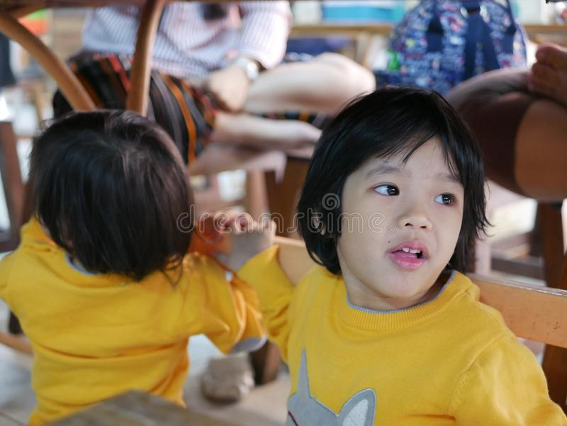 Little Asian baby girl sitting and playing / exploring with her younger sister under a dinning table at a restaurant royalty free stock photos