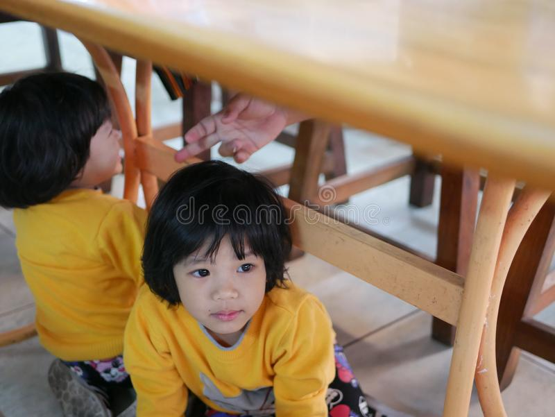 Little Asian baby girl sitting and playing / exploring with her younger sister under a dinning table at a restaurant - toddler royalty free stock images