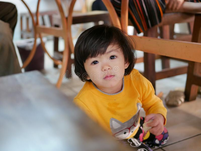 Little Asian baby girl sitting and playing / exploring under a dinning table during a meal with her family at a restaurant stock photo