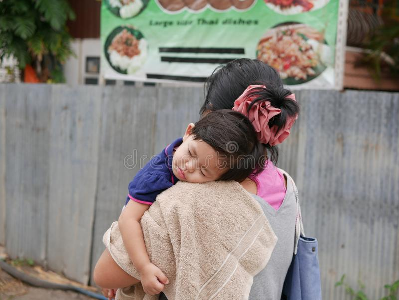 Little Asian baby girl sleeping on a shoulder of her auntie walking in a small alley stock photos