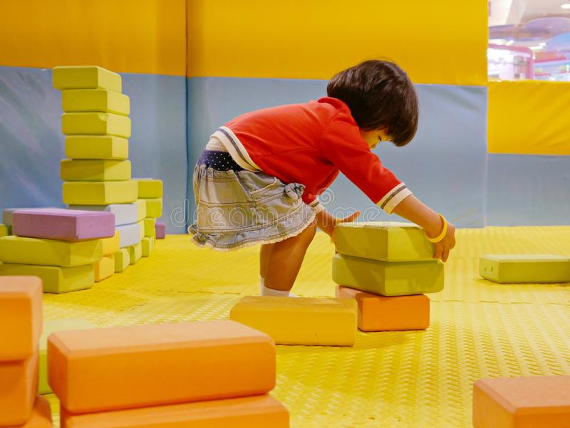 Little Asian baby girl stacking up foam building bricks / blocks at an indoor playground. Playing foam blocks helps develop children`s fine motor and logical royalty free stock photo