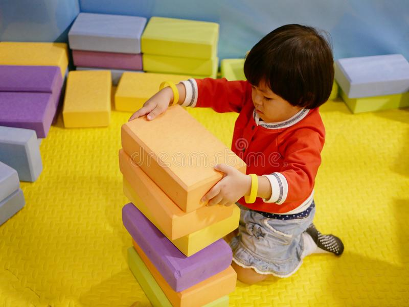 Little Asian baby girl stacking up foam building bricks / blocks at an indoor playground. Playing foam blocks helps develop children`s fine motor and logical royalty free stock photography