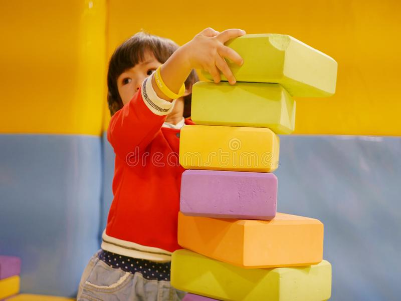 Little Asian baby girl stacking up foam building bricks / blocks at an indoor playground. Playing foam blocks helps develop children`s fine motor and logical stock photos
