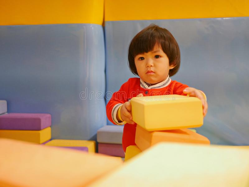 Little Asian baby girl stacking up foam building bricks / blocks at an indoor playground. Playing foam blocks helps develop children`s fine motor and logical royalty free stock photos