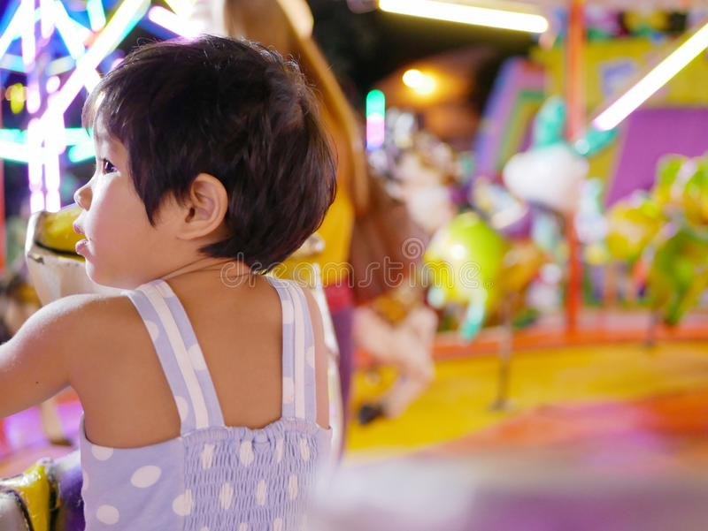 Little Asian baby girl taking a roundabout / carousel at a fair royalty free stock photo