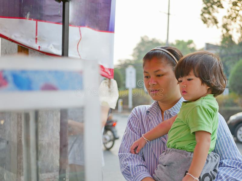 Little Asian baby girl together with her mother watching food vender selling / cooking street food royalty free stock image
