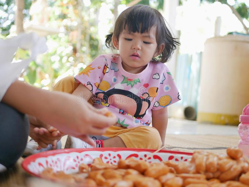 Little Asian baby girl watching her mother putting hot dogs on each wooden stick stock images
