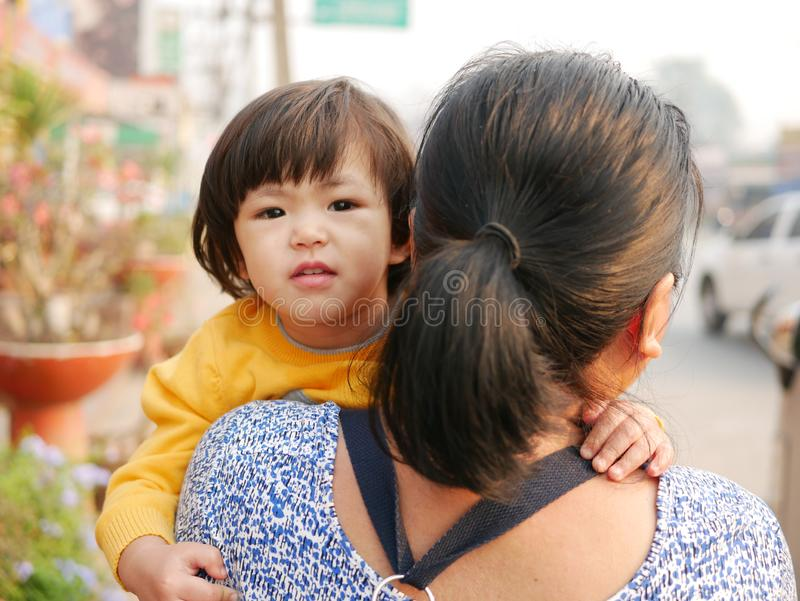 Little Asian baby girl, 2 years old, enjoys being carried by her auntie walking on the roadside.  royalty free stock photography