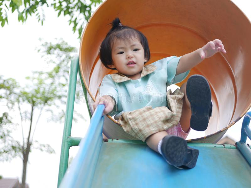 Little Asian baby girlenjoys playing a slider at a playground. Ttle Asian baby girl, 18 months old, enjoys playing a slider at a playground. - large muscle and royalty free stock image