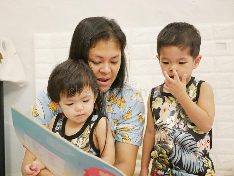 Little Asian baby girls enjoy having their mother reading a book aloud to them stock images