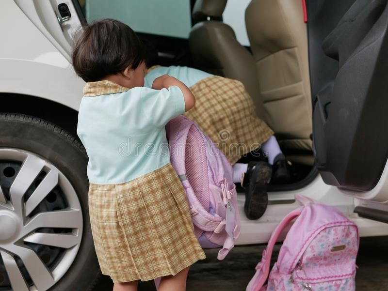 Little Asian baby girls learning to carry her school bag and get into the car by herself stock image