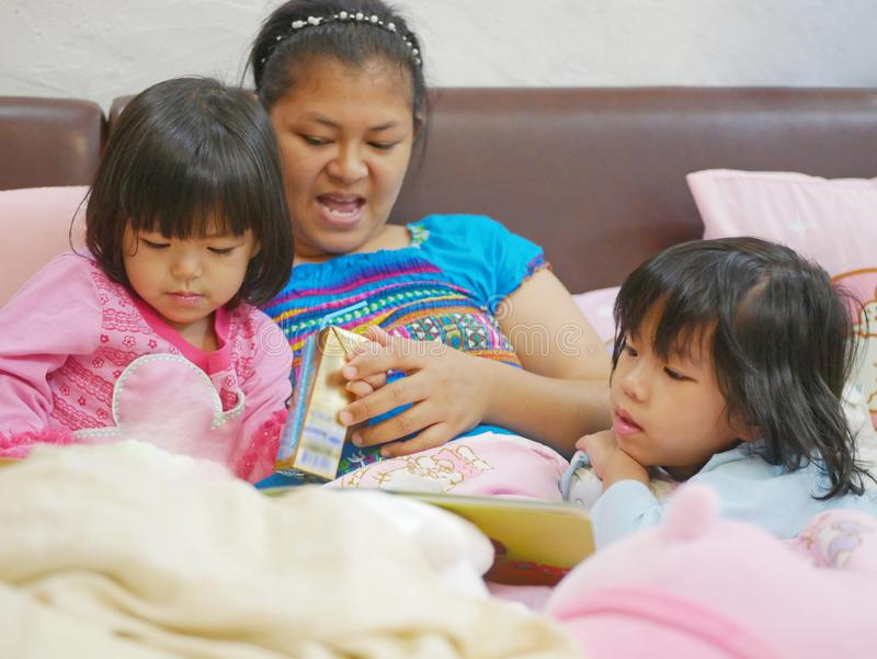 Little Asian baby girls, sisters, enjoys drinking milk and listening to her mother reading a fairy tale book before her bedtime stock images