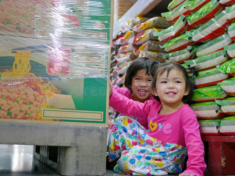Little baby girls, sisters, playing / hiding behind a big boxes of instant noodles at a supermarket - hide and seek royalty free stock photos