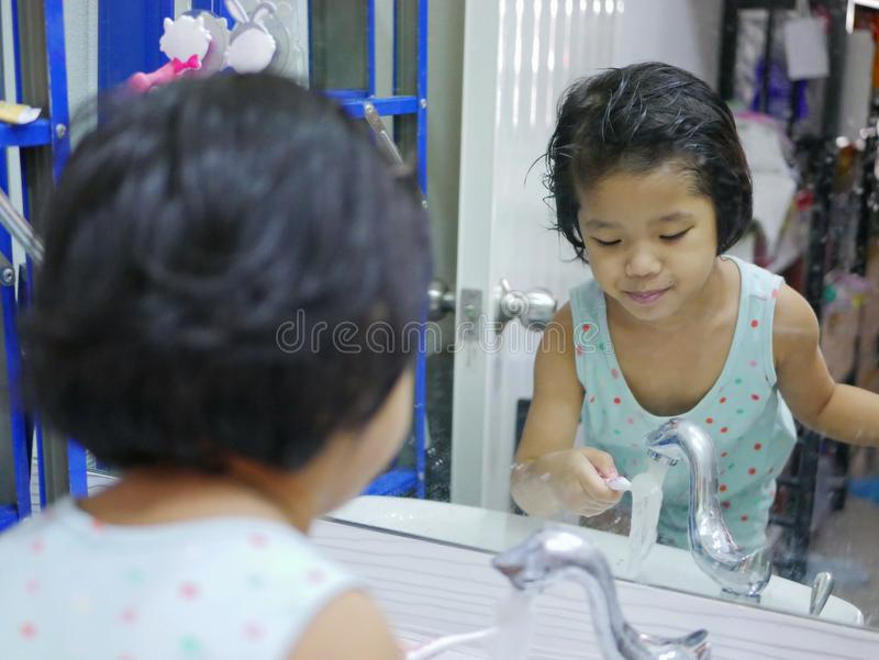 Little Asian baby girl washing her toothbrush in front of a mirror by herself stock photo