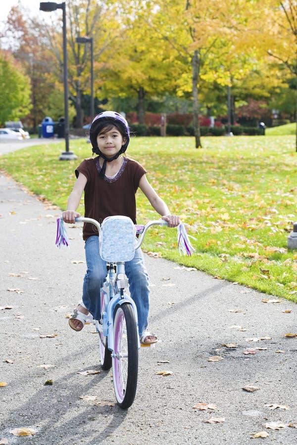 Little Asian biracial girl riding bike in park