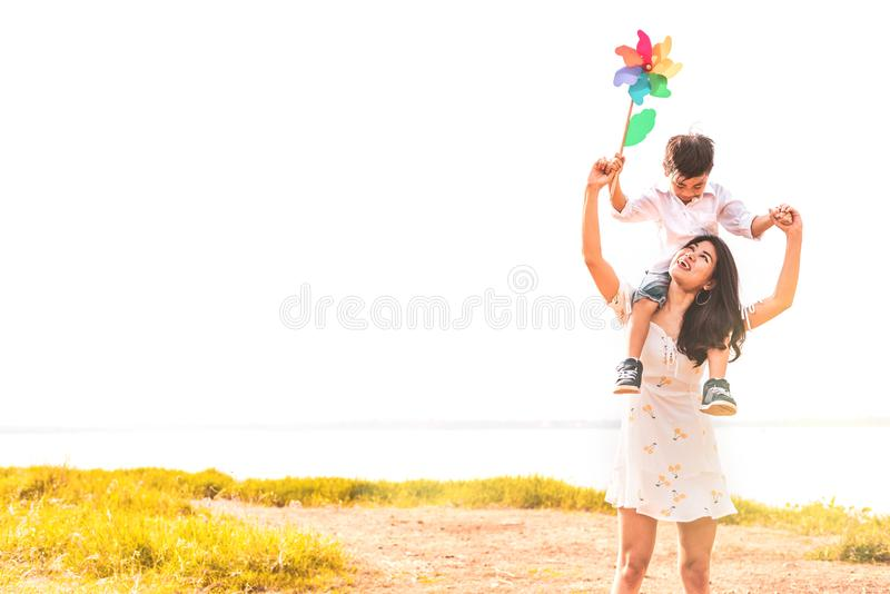 Little Asian boy riding back on his super power mom in meadow near lake. Mother and son playing together. Celebrating in Mother stock photos