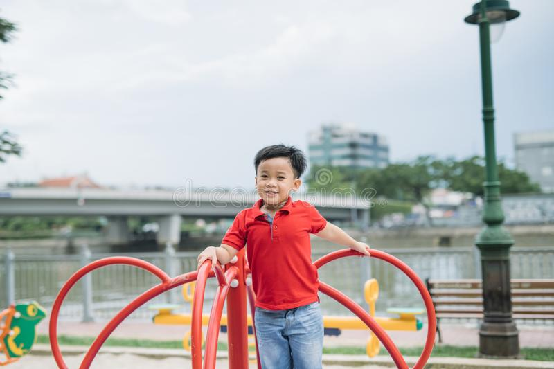 Little asian boy riding a swing and rejoices.  stock images