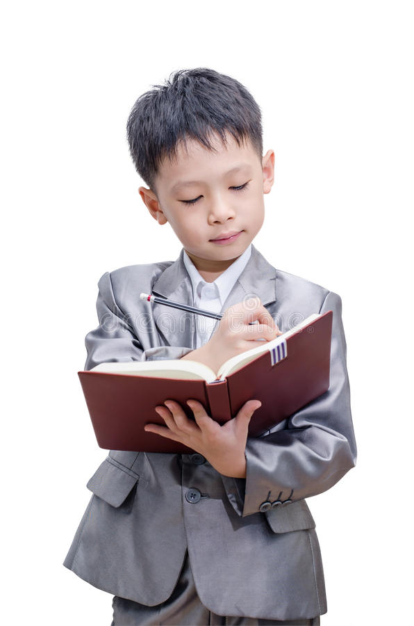 Little Asian boy in suit standing with a diary. Isolated over white background stock image