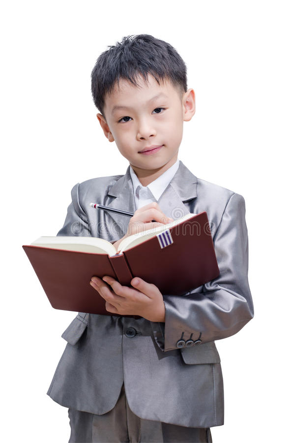 Little Asian boy in suit standing with a diary. Isolated over white background royalty free stock photo