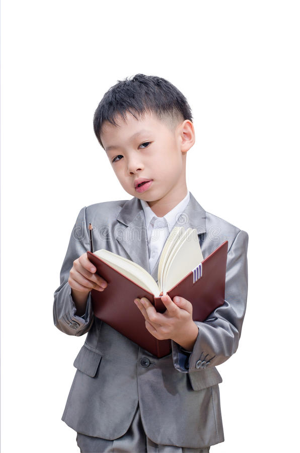 Little Asian boy in suit standing with a diary. Isolated over white background royalty free stock photos