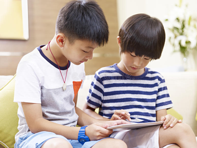 Little asian brothers using digital tablet together royalty free stock photos