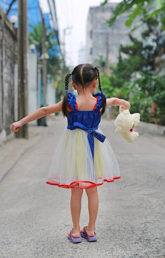 Little Asian child girl dressed a fantasy outfit with holding teddy bear standing alone in alley stock image