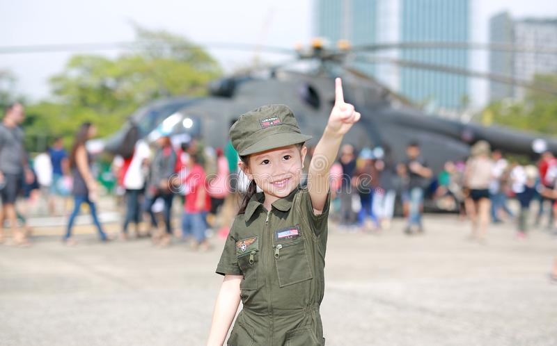Little Asian child girl in pilot soldier suit costume with holding gun in hand and pointing up against aircraft background stock photo
