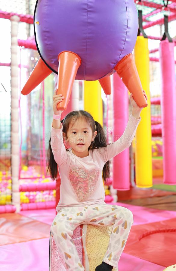 Little Asian child girl playing in indoors playground. Active girl having fun at sport center on holiday.  stock photography