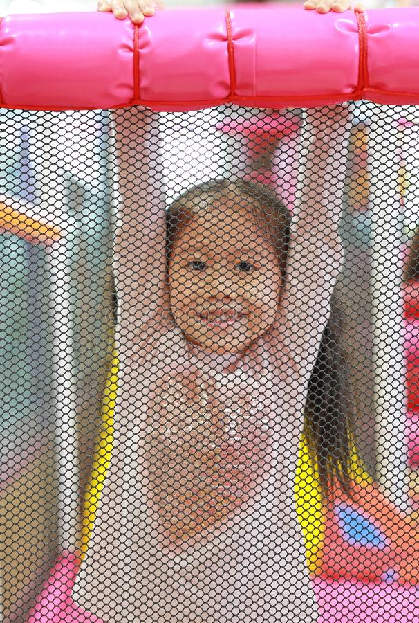 Little Asian child girl rear a net playing and hanging in indoors playground. Active girl having fun at sport center on holiday.  royalty free stock photo