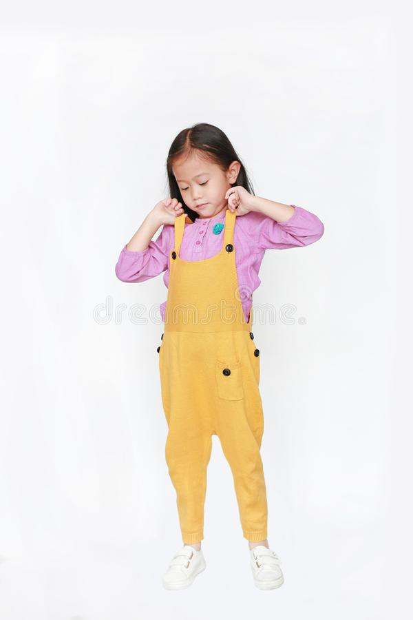 Little Asian child girl wearing a yellow dungarees isolated on white background royalty free stock photos