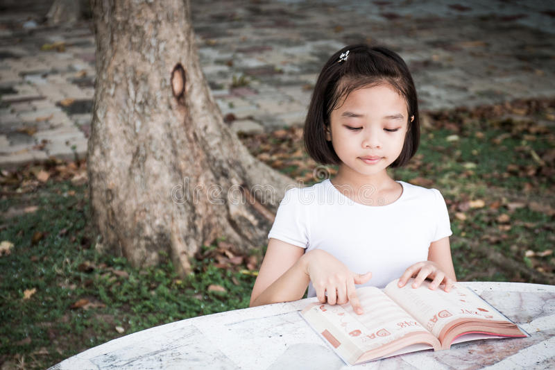 Little Asian child reading a book. Outdoor stock photo