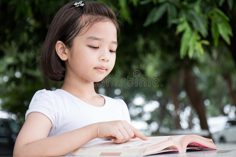 Little Asian child reading a book. Outdoor stock image