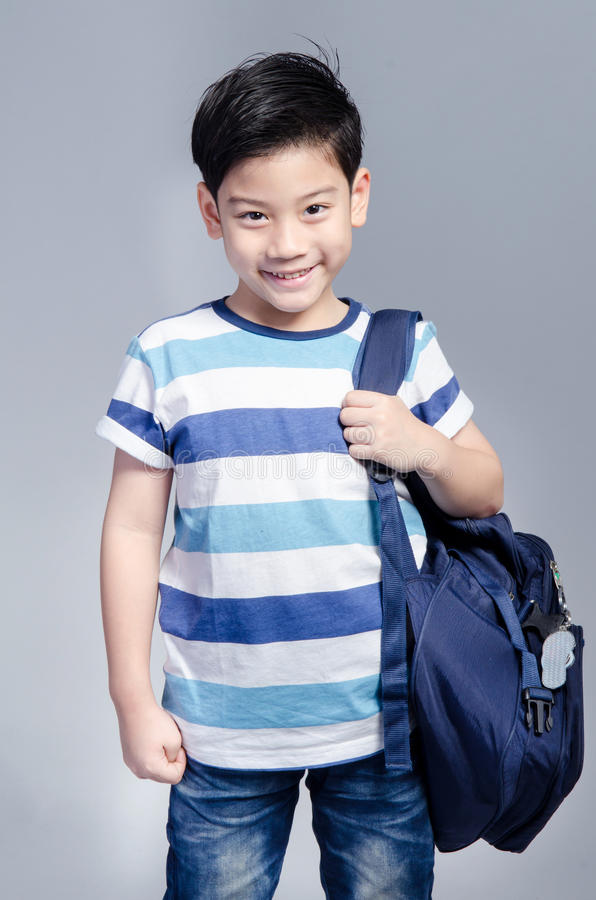 Little Asian child standing with a kit bag slung over his should stock photos