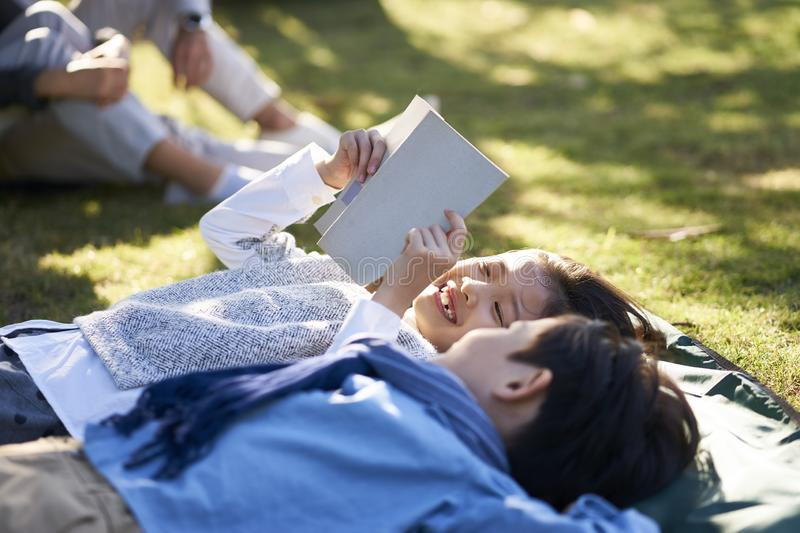 Little asian children lying on grass reading royalty free stock photography