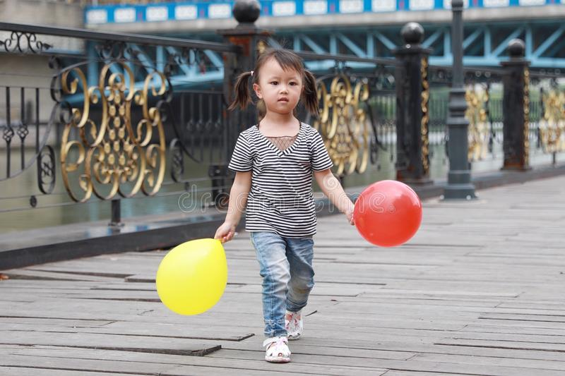 Asian Chinese cute naughty lovely adorable girl play with balloon and have fun outdoor in summer park happy smile walk on street royalty free stock image