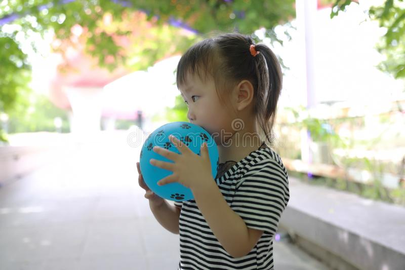 Aisa cute naughty lovely adorable child girl play with balloon have fun outdoor in summer park happy smile happiness childhood royalty free stock image