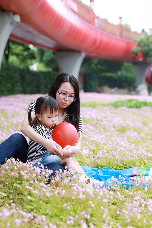 Happy family parental child time mother love children daughter play with baby girl blew balloon together have fun in summer park. A little Asian Chinese girl royalty free stock photos
