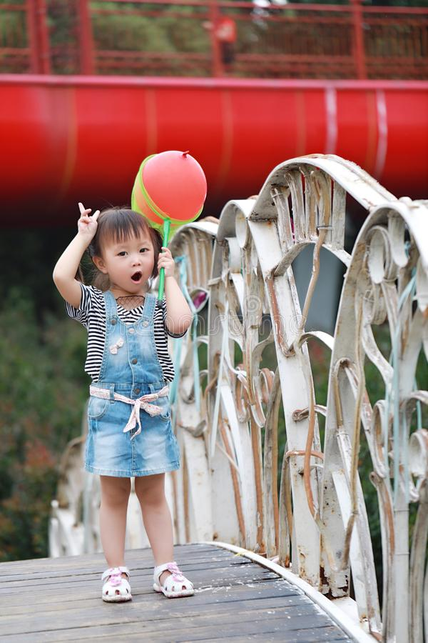 Aisa cute naughty lovely child girl play with balloon have fun outdoor in summer park happy smile happiness funny childhood stock photo