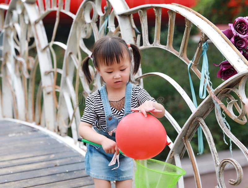 Aisa cute naughty lovely child girl play with balloon have fun outdoor in summer park happy smile happiness funny childhood stock photography