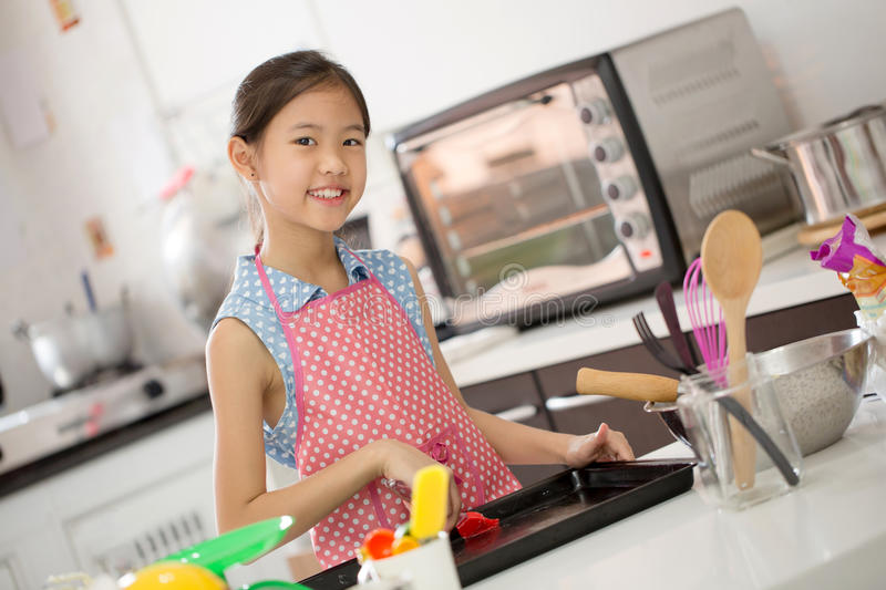 Little Asian cute chef cooking a bakery in kitchen royalty free stock photos