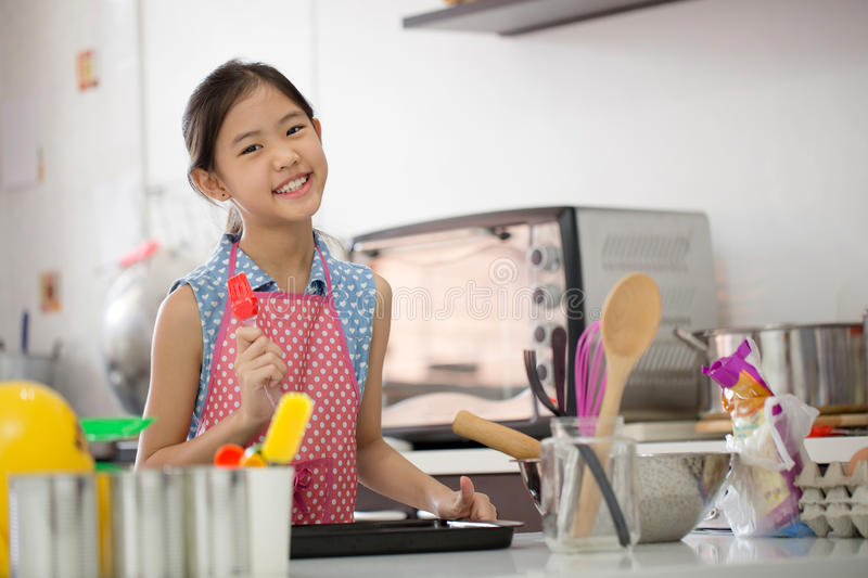 Little Asian cute chef cooking a bakery in kitchen royalty free stock images