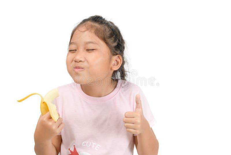Little asian cute girl eats banana isolated royalty free stock photo