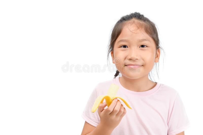 Little asian cute girl eats banana isolated on white stock image
