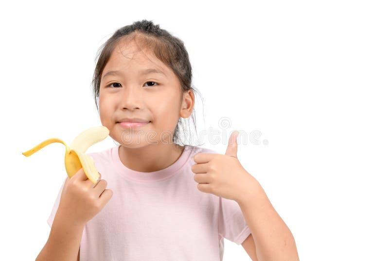 Little asian cute girl eats banana isolated stock image