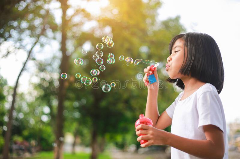 Little Asian girl blowing bubbles in the garden. stock photo