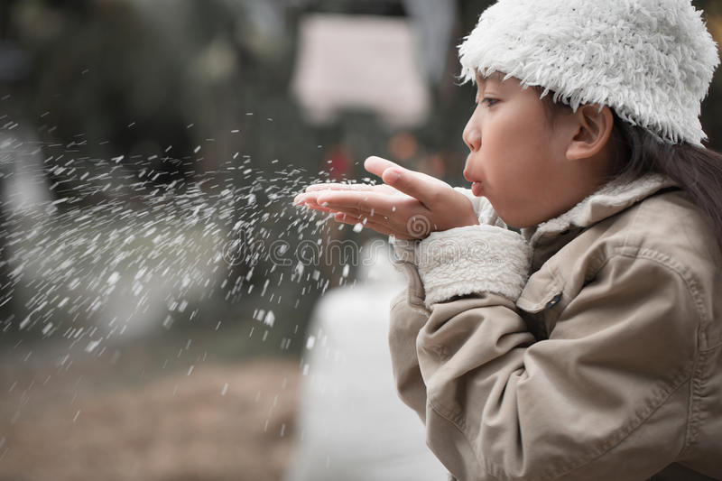 Little asian girl blowing snowflake moving forward with children stock images